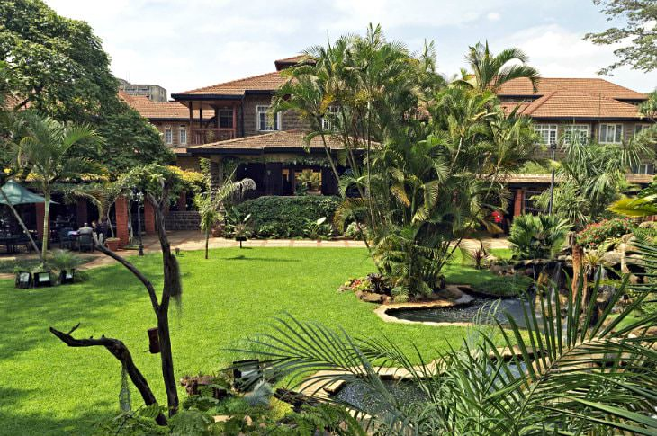 Wood-sided hotel surrounded by green grass, ponds, and tropical plants and trees