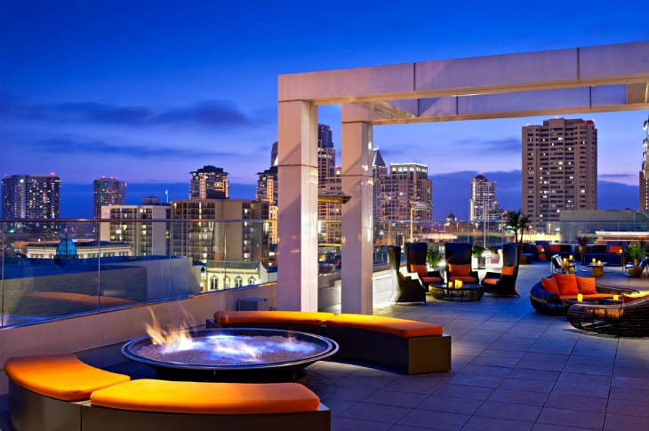 Roof top bar with modern, organically shaped seating and fire pits overlooking a city skyline at dusk