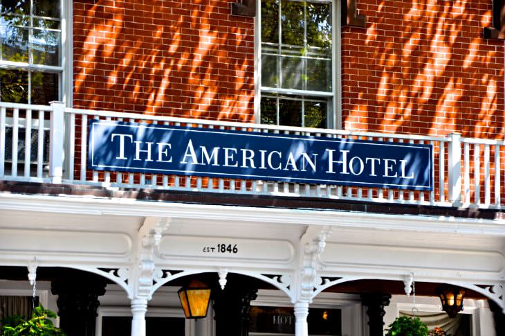 Close-up view of the American Hotel sign on a brick building with a white covered porch