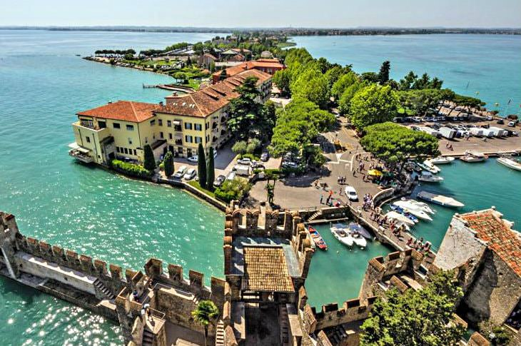 Luxury hotel on a peninsula surrounded by turquoise water next to a medieval castle