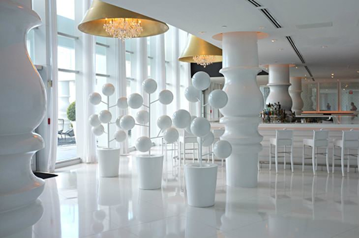Interior view of a clean, modern, all-white hotel bar area