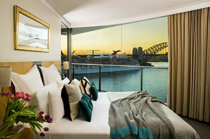 Simple and elegant beige guest room with glass wall overlooking Sydney Harbour Bridge