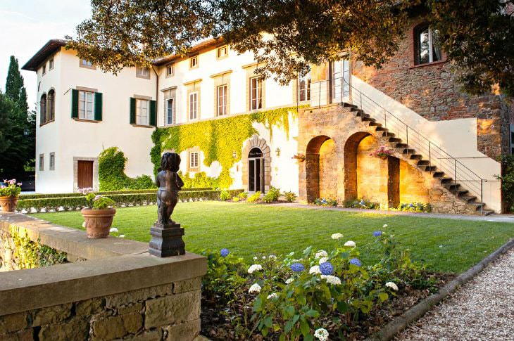 Tuscan hotel with arched windows and doorways, small green lawn surrounded by stone wall with flowers and statues