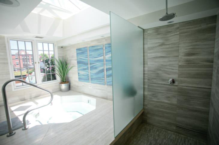 Modern tiled room with jacuzzi sunlit by large skylight next to a walk-in shower with rain shower head
