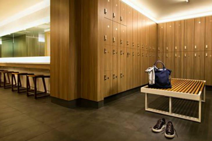 Upscale brown and beige locker room with one pair of tennis shoes and a blue gym bag
