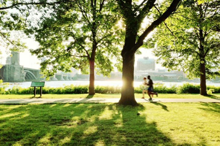 Two people jogging on a path surrounded by green grass and trees with Boston harbor and bridge in the background
