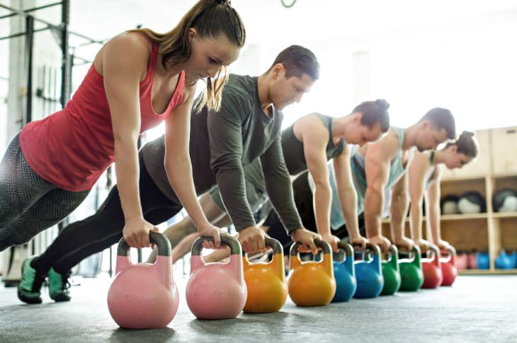 Five men and women doing push-ups on pink, orange, blue, green and red medicine balls