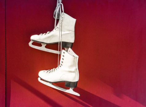 two white ice skates hanging on a red background