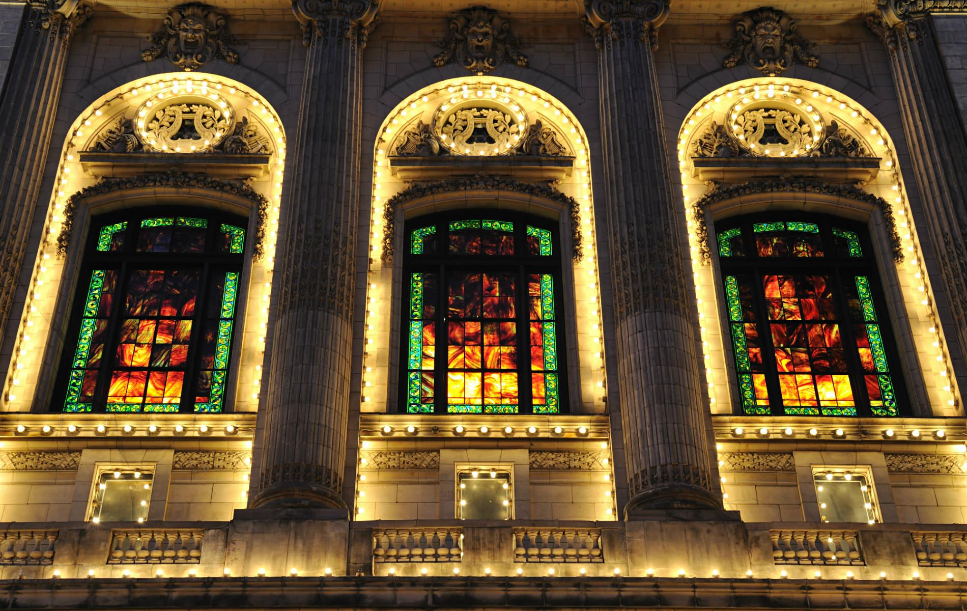 Ornately carved stone building lit up at night with tall arched windows, Grecian columns, stained glass