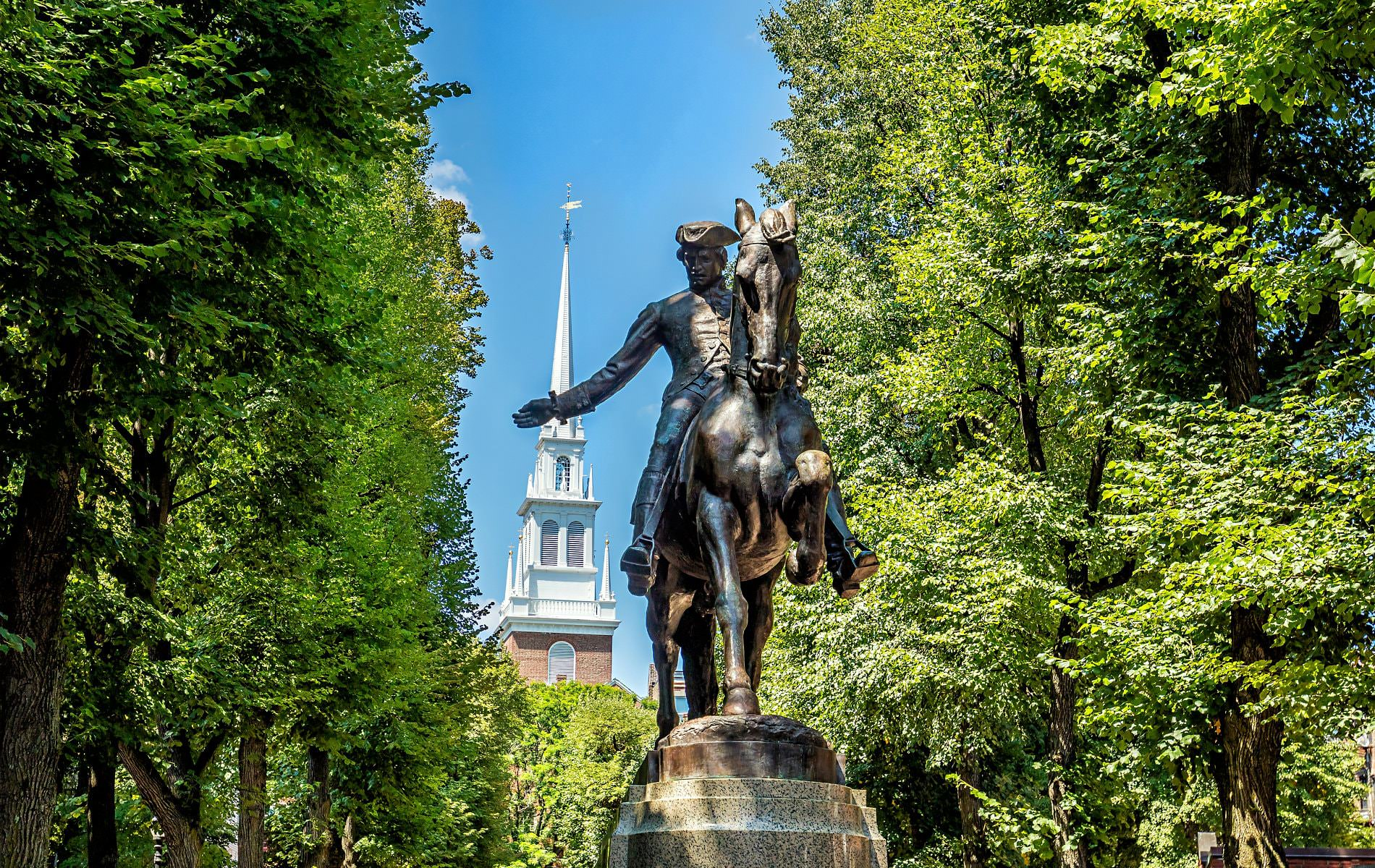 Statue of Paul Revere surrounding by lush green trees with blue skies and a white steeple in the background