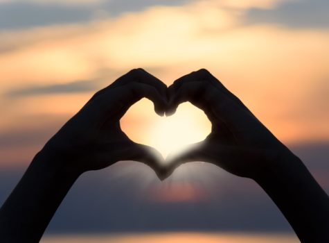 two hands in the shape of a heart with a sunset