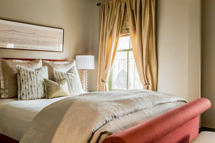 Warm elegant beige room with luxurious bedding, coral colored head and footboards, and window with gold curtains