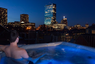 man in hot tub with blue lights and city skyline at night