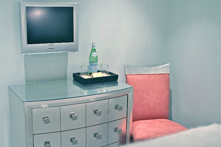 Silver room with mirrored chest, flat screen TV, and pink and silver chair