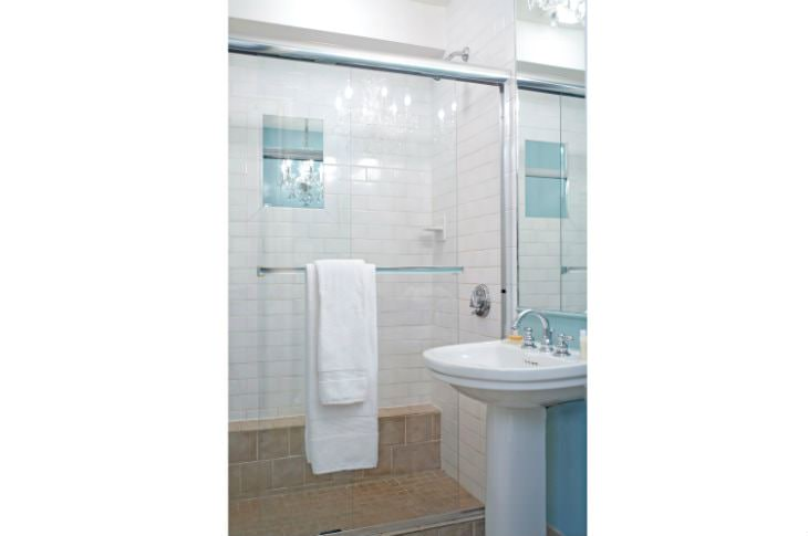 White and light blue bathroom with white tiled walk-in shower, glass doors and white pedestal sink