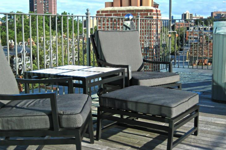 Roof top deck with black and gray chairs and ottoman and silver metal railing overlooking the city