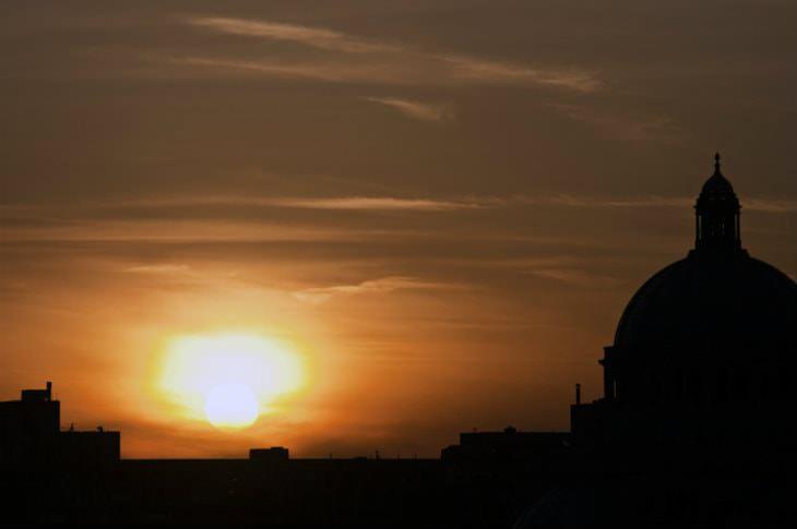 Black silhouette of buildings against a beautiful orange sunset