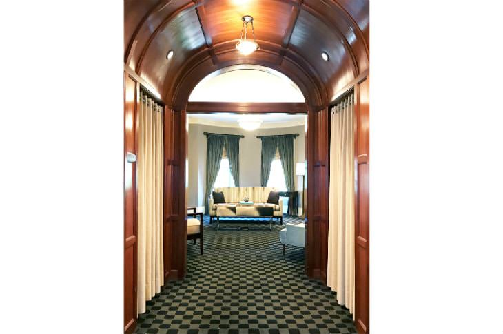 Hallway with stained wood barrel vault ceiling, checkered carpeting and view of sitting area in the background