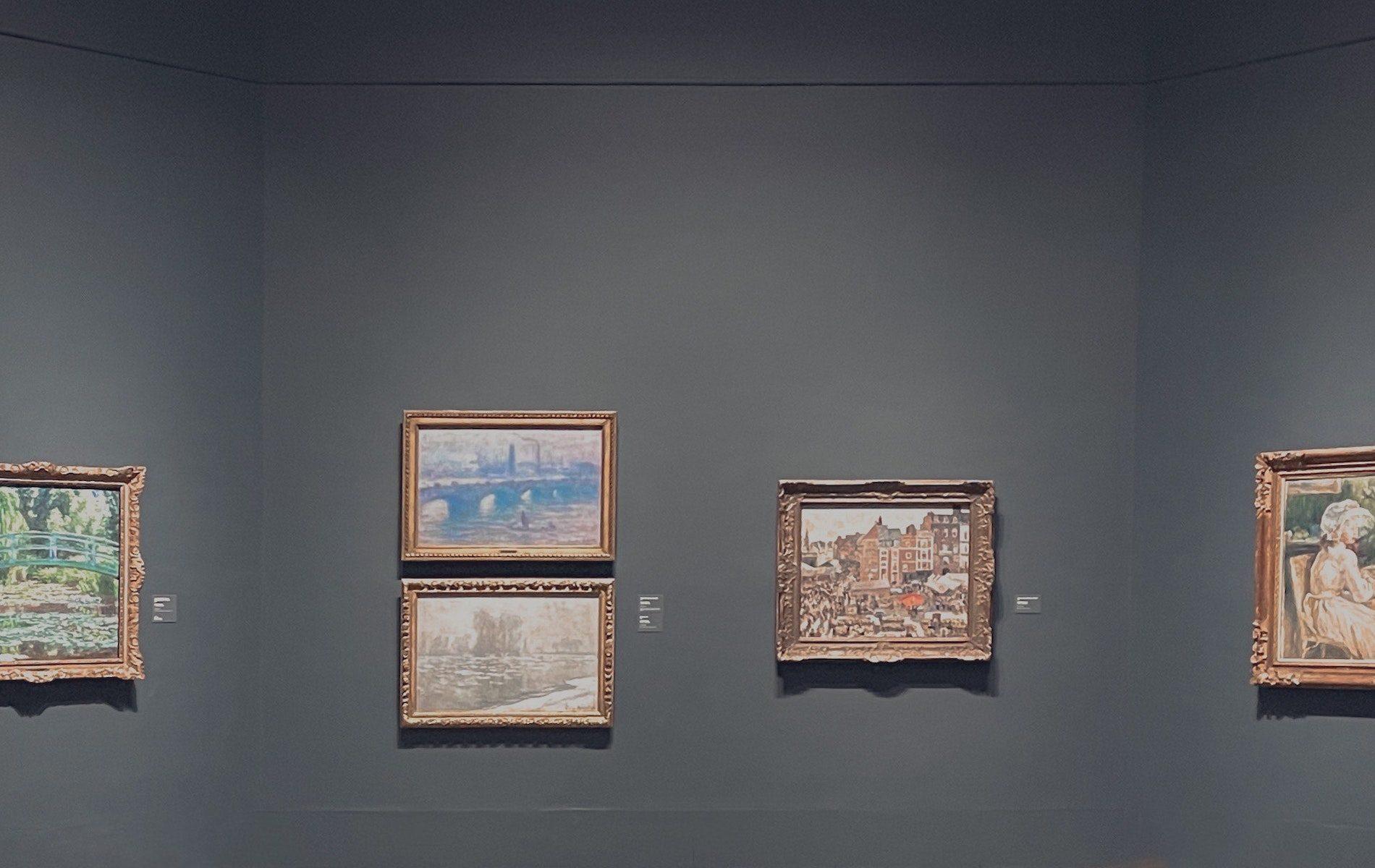 5 framed monet painting on dark grey wall