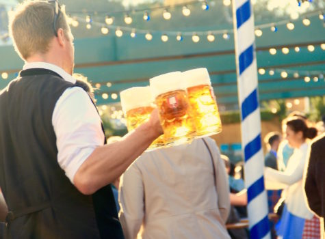 man in black vest carrying 3 large glass beer mugs in party next to a white and blue stripe poll