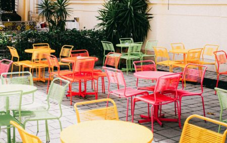 clusters of yellow, red, orange and green table and chairs outside on grey pavers