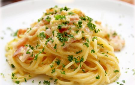 pasta boodles with green parsley on white plate