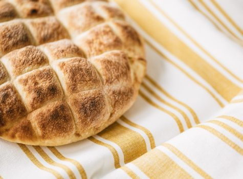golden brown pita with checked designed on gold and white stripe towel