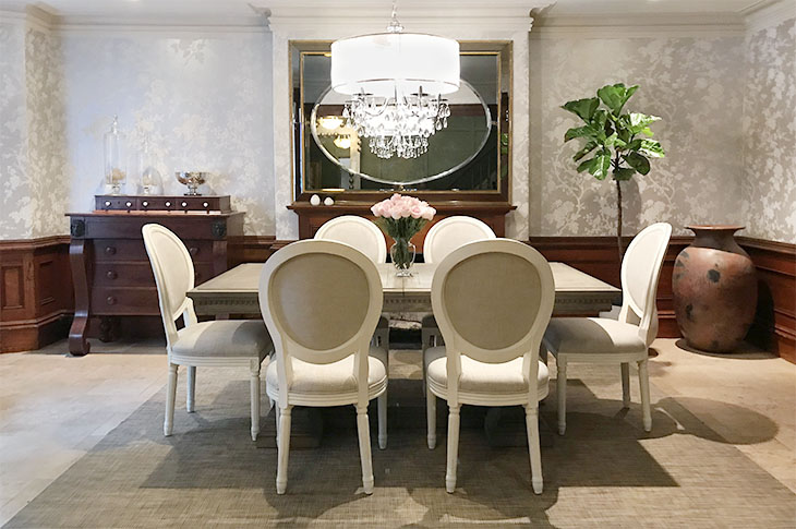 Dining room with silver wallpaper, mahogany paneling, oak table and 6 white and linen chairs.