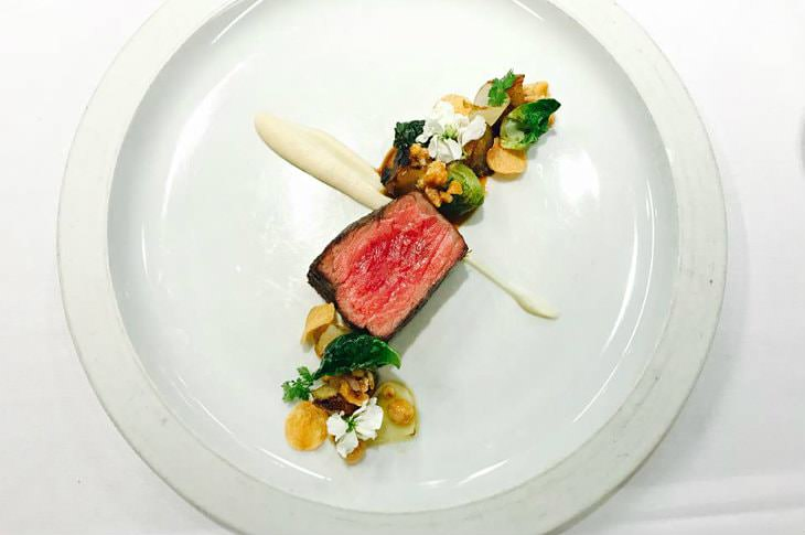 Artistic gourmet dish of seared meat sprinkled with green and white flowers on a white plate