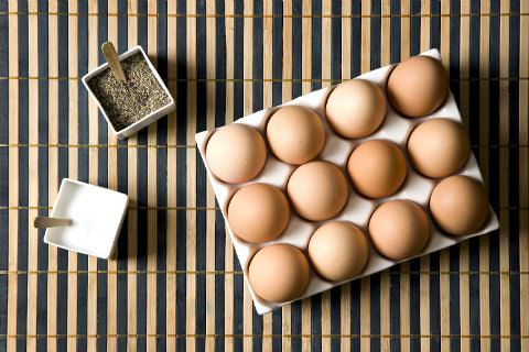 Three white containers of a dozen brown eggs, salt, and pepper on a bamboo placemat