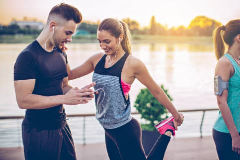 Man and woman in black workout clothes wearing ear buds getting ready to run alongside a body of water