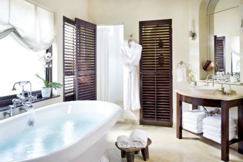Beige bathroom with tile floor, freestanding white tub, wood vanity with vessel link, white towels and white robe
