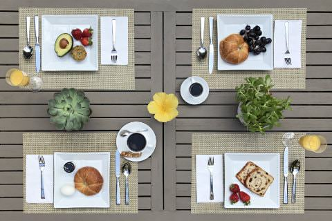 Gray patio table set for four with different breakfast plates of strawberries, avocado, croissants, blueberries, toast, juice, and coffee