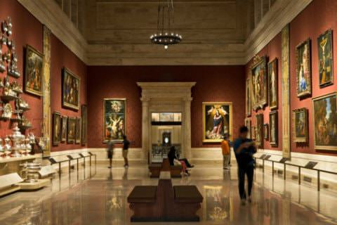 Elegant gallery with shiny marble floors and red walls filled with artwork