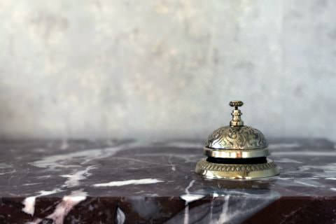 Close-up view of a gold ornate service bell on a stone countertop