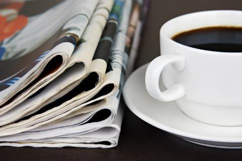 Stack of folded newspapers next to a white cup and saucer filled with coffee