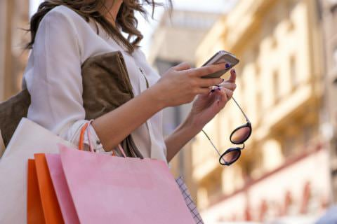 Woman with white, pink and orange shopping bags on her arm, holding her sunglasses, looking at her cell phone