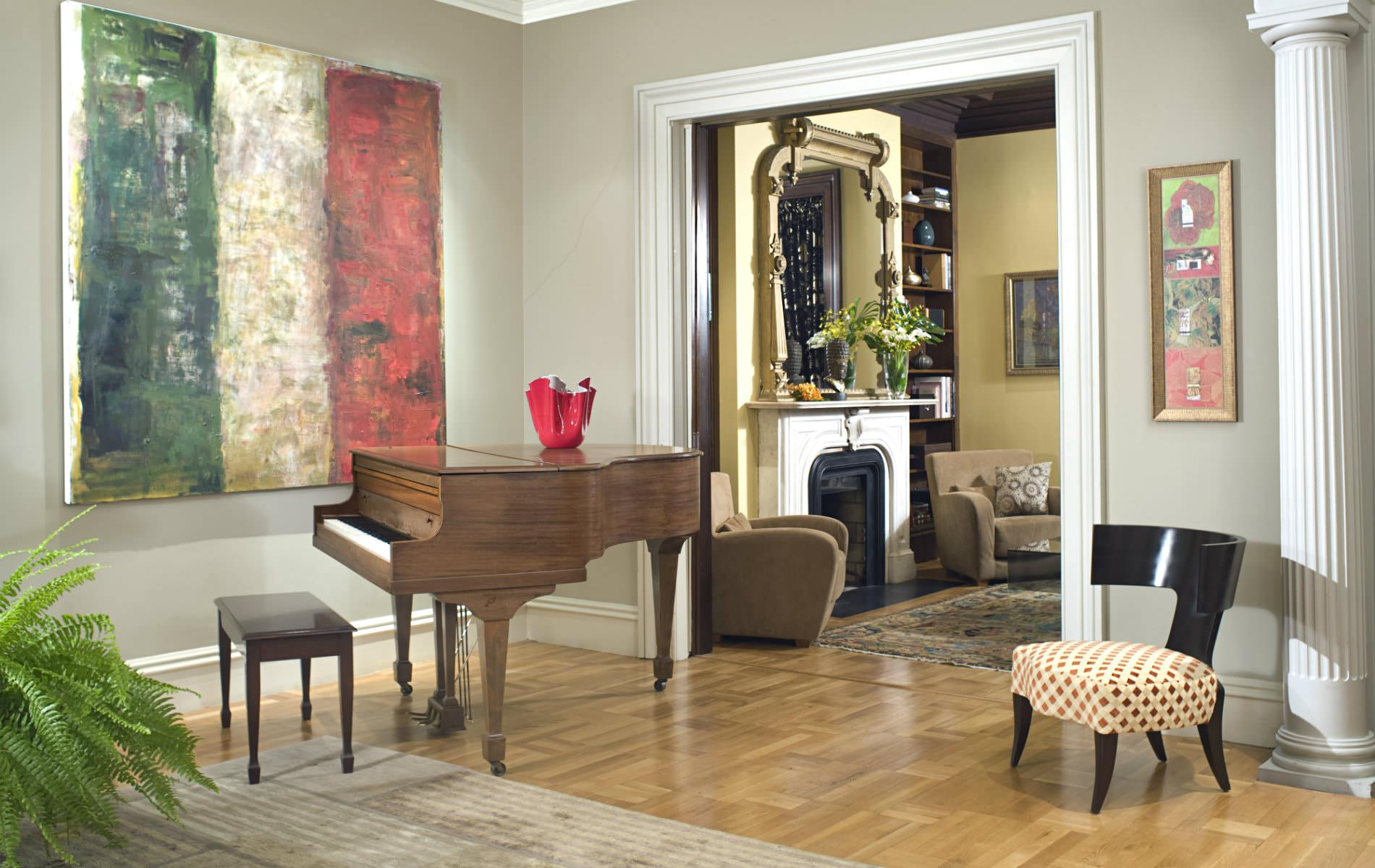 gray painted room, light wood floors, large abstract wall hanging and stained wood grand piano