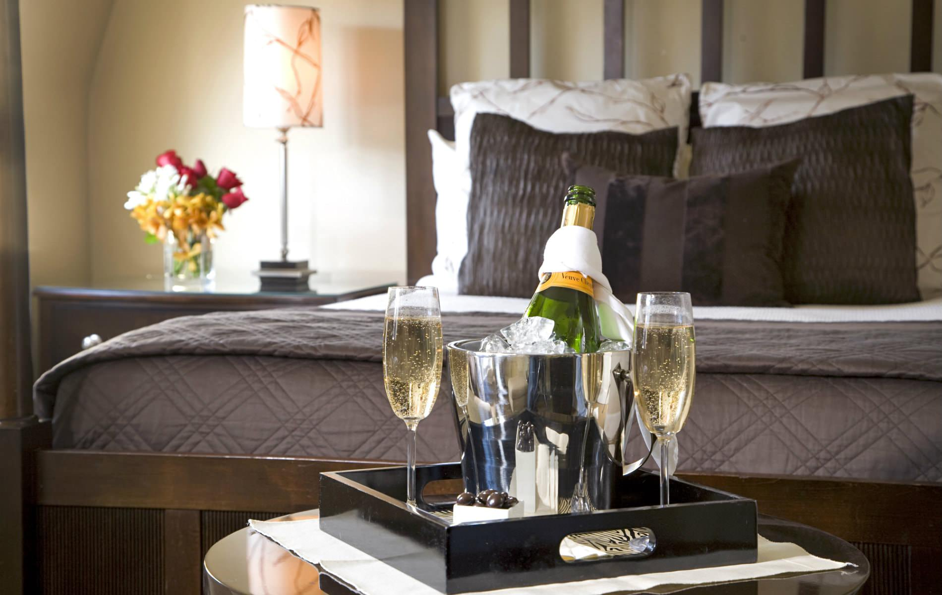 Black tray of champagne chilling in silver bucket and two filled champagne flutes with view of elegant bed in background