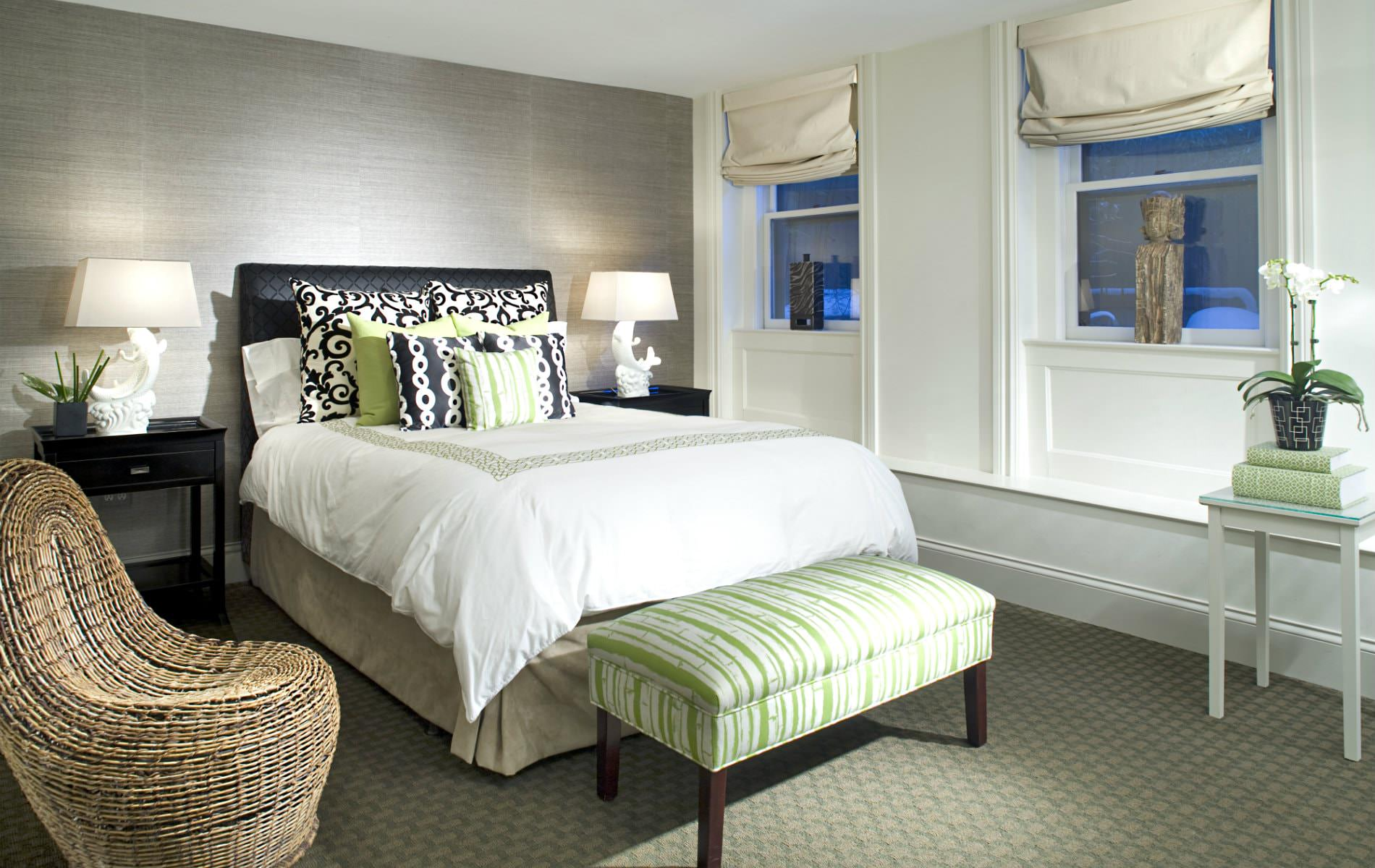 Elegant guest room with black, lime green and white bed, lime green bench, wicker chair, and two windows