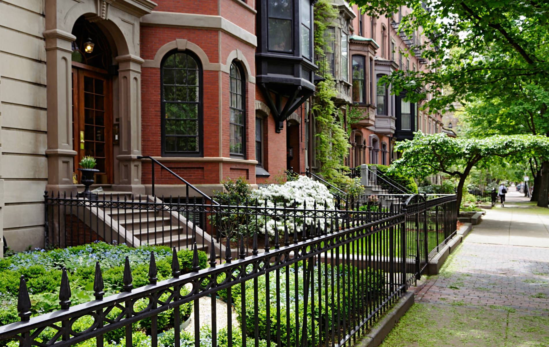 Row of red and brown brick brownstones behind black wrought iron gates