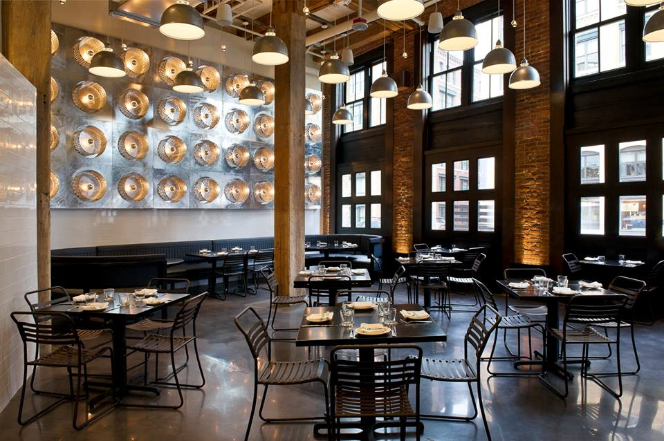 industrial restaurant with 4 tables and concrete floors and grid of lights on the brick wall