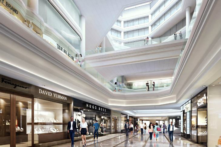 Elegant mall aisle of stores with multiple floors, white columns and glass railings