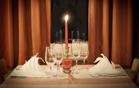 White table cloth table set for two with a red candle and red curtains