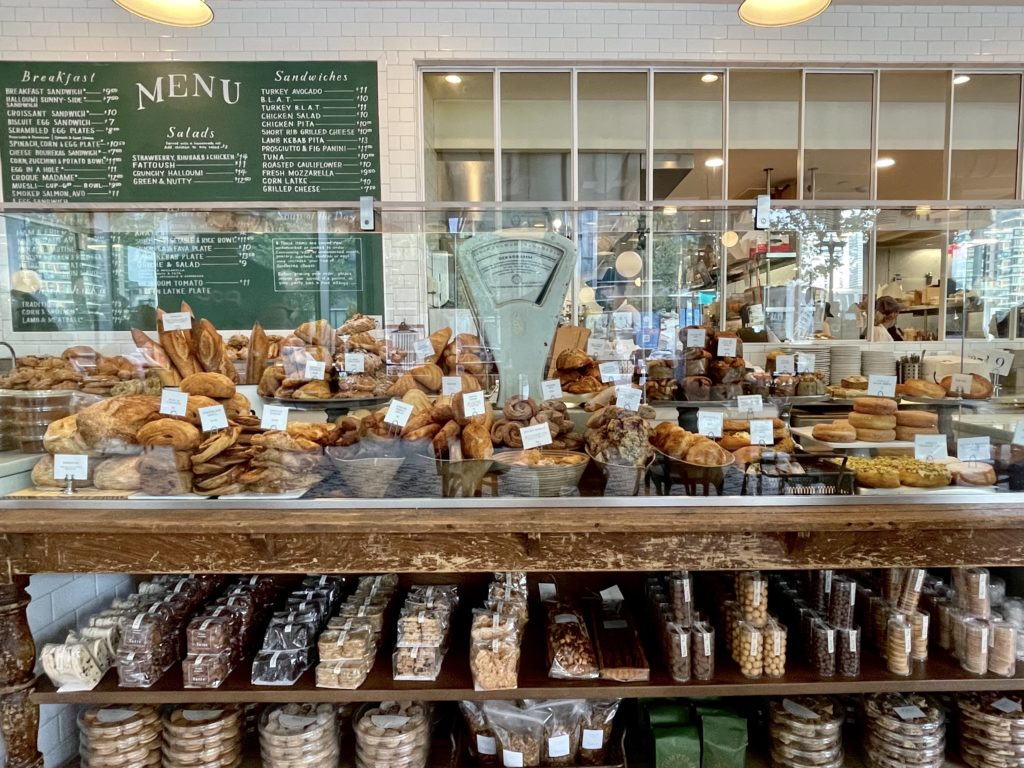 wooden table with glass partition containing pastries, croissants, scones, muffins on top, and rows of cookies biscotti and biscuits on shelf below green chalk board with white letters behind