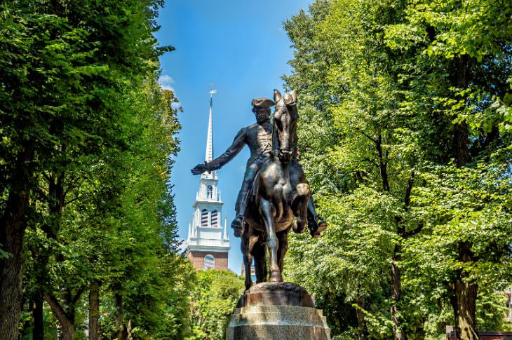 Bronze statue of Paul Revere surrounding by lush green trees with blue skies and a white steeple in background