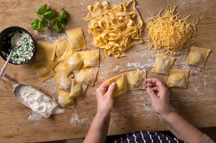 Woman's hands making homemade pasta and noodles on a wooden table dusted with white flour