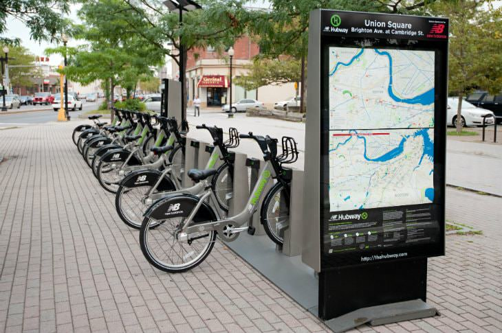 Boston Hubway station with several silver and lime green bikes available for rent
