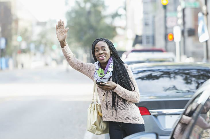 Woman wearing dark jeans and tan sweater waving toward a taxi while holding a cell phone